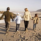 rear view of a mid adult couple walking on the beach with their children