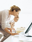 side profile of a businesswoman carrying her daughter and using a computer