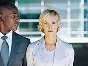 portrait of a businesswoman with a businessman looking at her