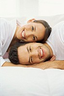 portrait of a young couple lying on a bed and smiling