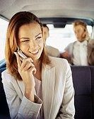 businesswoman talking on a mobile phone with two businessmen sitting at the back of a car