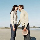 side profile of a mid adult man and a young woman standing face to face on the beach