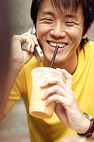 Young man on the phone, holding cup and smiling