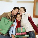 portrait of parents with their daughter holding gifts