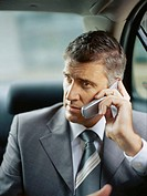 businessman talking on a mobile phone in a car