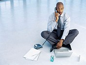 high angle view of a businessman sitting in front of a laptop and talking on a telephone in an office