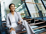 businesswoman holding a mobile phone in an office