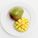 close-up of a mango and a slice of mango on a plate
