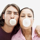 close-up of a young couple blowing chewing gum bubbles