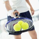 mid section view of a young man holding tennis balls over a racket