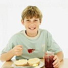 portrait of a boy putting jam with a spoon on bread