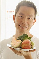 Man holding fruits and vegetables on a plate, looking at camera