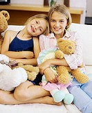Portrait of two sisters holding toys and smiling