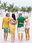 Rear view of four mature people standing on the beach