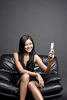 Young woman on black chair, looking at camera phone