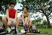 Two men on park bench, putting on roller blades, side by side