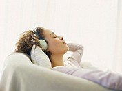 Side profile of a young woman wearing headphones and listening to music