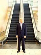 Portrait of a businessman standing in front of an escalator