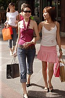 Two women, walking arm in arm, carrying shopping bags