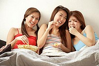 Young women sitting side by side, eating popcorn and watching TV