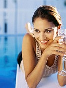 Close-up of a young woman lying on a diving board holding a champagne flute