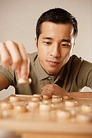Man playing Chinese chess, concentrating