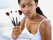 Close-up view of a young woman holding make-up brushes