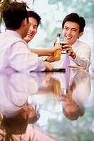 Young men with drinks, toasting
