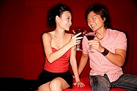 Couple toasting with drinks, looking at each other
