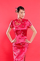 Woman in Cheongsam, hand on hips, looking away