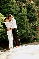 Couple standing in park, hugging, looking at camera