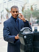 Businessman on mobile phone and putting money in parking meter