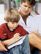 Close-up of a father helping his son with his homework