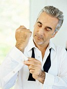 Close-up of a mature man buttoning the cuff of his shirt