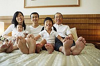 Three generation family on bed, looking at camera, low angle view