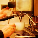 Waiter making a coffee using a coffee maker
