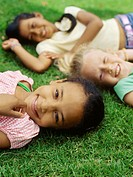 Portrait of three girls lying on grass and smiling