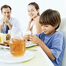 Young man sitting at the breakfast table with a young boy (6-8) and a teenage girl (13-15)