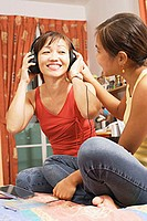 Mother and daughter side by side, mother listening to headphones