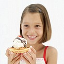 Young girl (8-9) holding ice-cream dessert