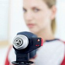 Close-up of a woman pointing a drill at the camera (blurred)