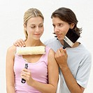 Young couple holding a paint brush and paint roller