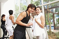 Couple in gym, looking at camera, people in the background