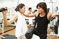 Couple working out in gym, weight training, people in the background