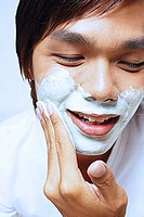 Young man applying shaving foam on face, looking down