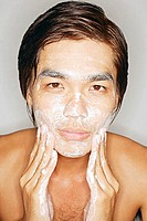 Young man washing face, looking at camera