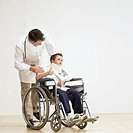 Elderly male doctor wheeling a young boy (8-10) in a wheelchair