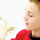 Side profile of a teenage boy (15-17) peeling a banana
