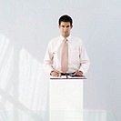 Young businessman standing at a podium