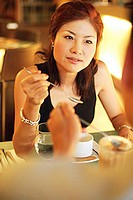 Woman in restaurant holding spoon